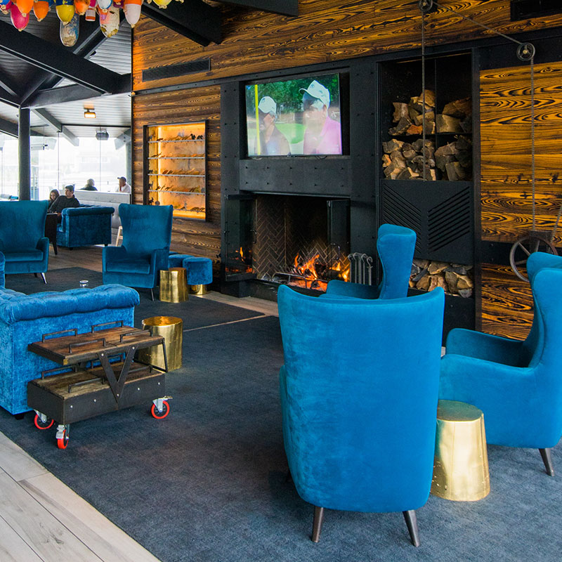 Restaurant lobby showcasing five blue velvet chairs facing each other with a wood grain wall that holds a mounted tv, firewood, and a burning fireplace