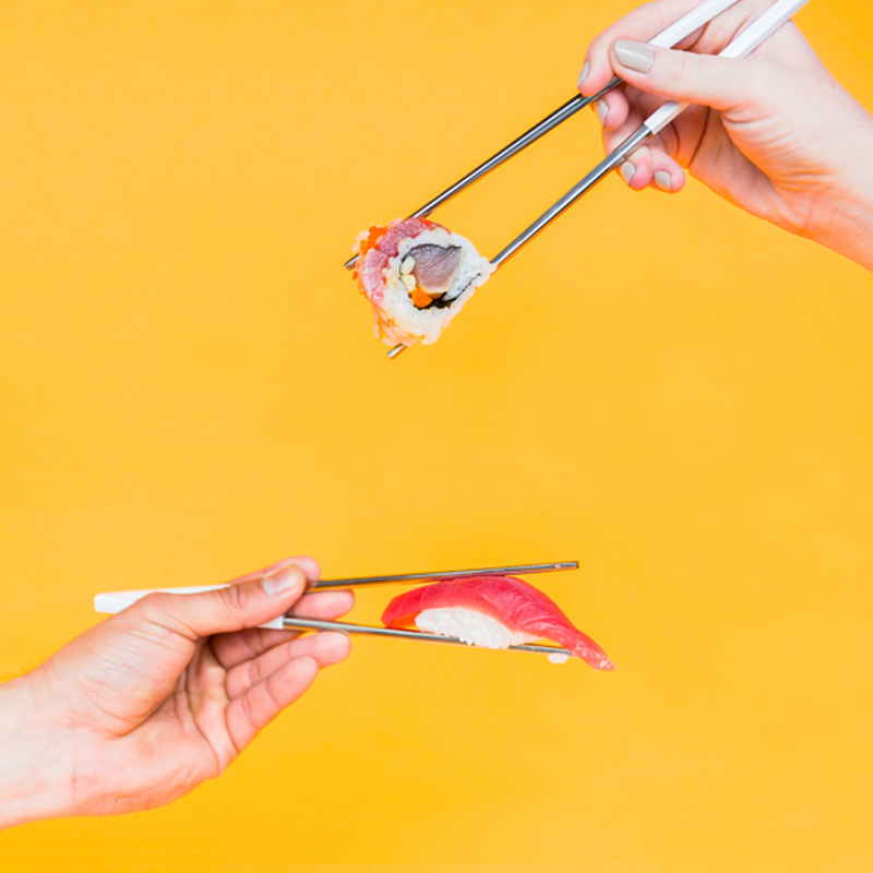 Two hands holding sushi with chopsticks against an orange background