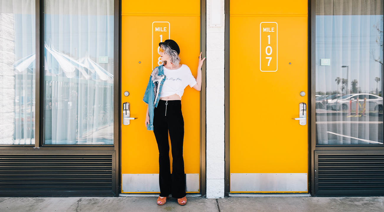 Girl in black pants standing in front of yellow motel door with mile marker sticker graphic