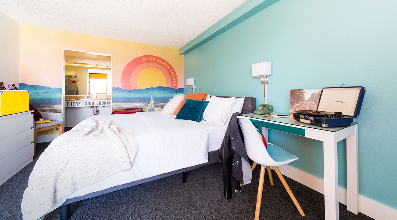 Interior of Rambler Motel guest room with Here Comes the Sun wall graphic