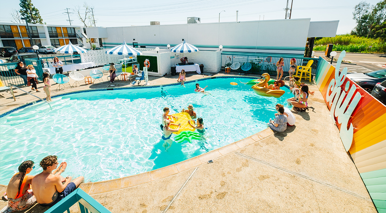 Rambler pool area with colorful Chill sign and guests on rafts in the water