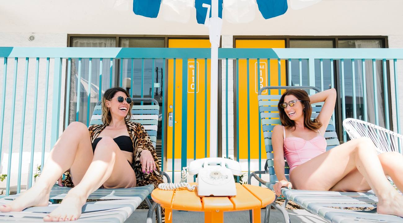 Two girls laughing and lounging on chairs at The Ramblers pool