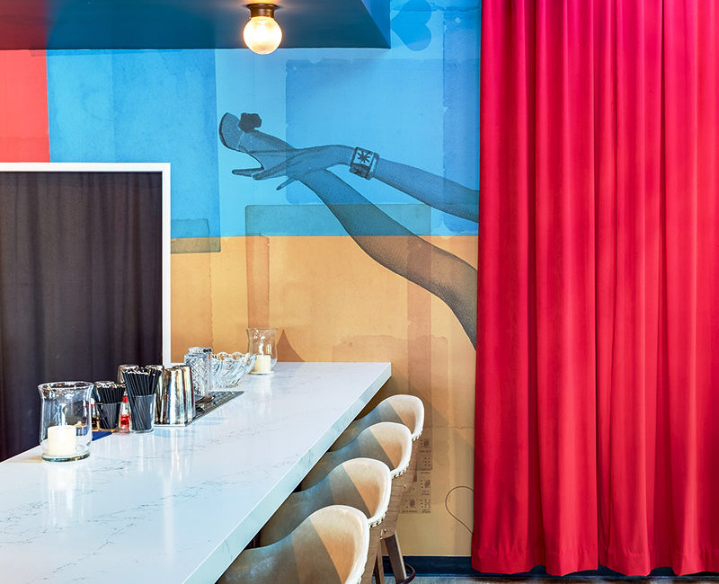 Bar table with cream chairs against a blue and gold background printed with a showgirl's leg peeking out of a red curtain
