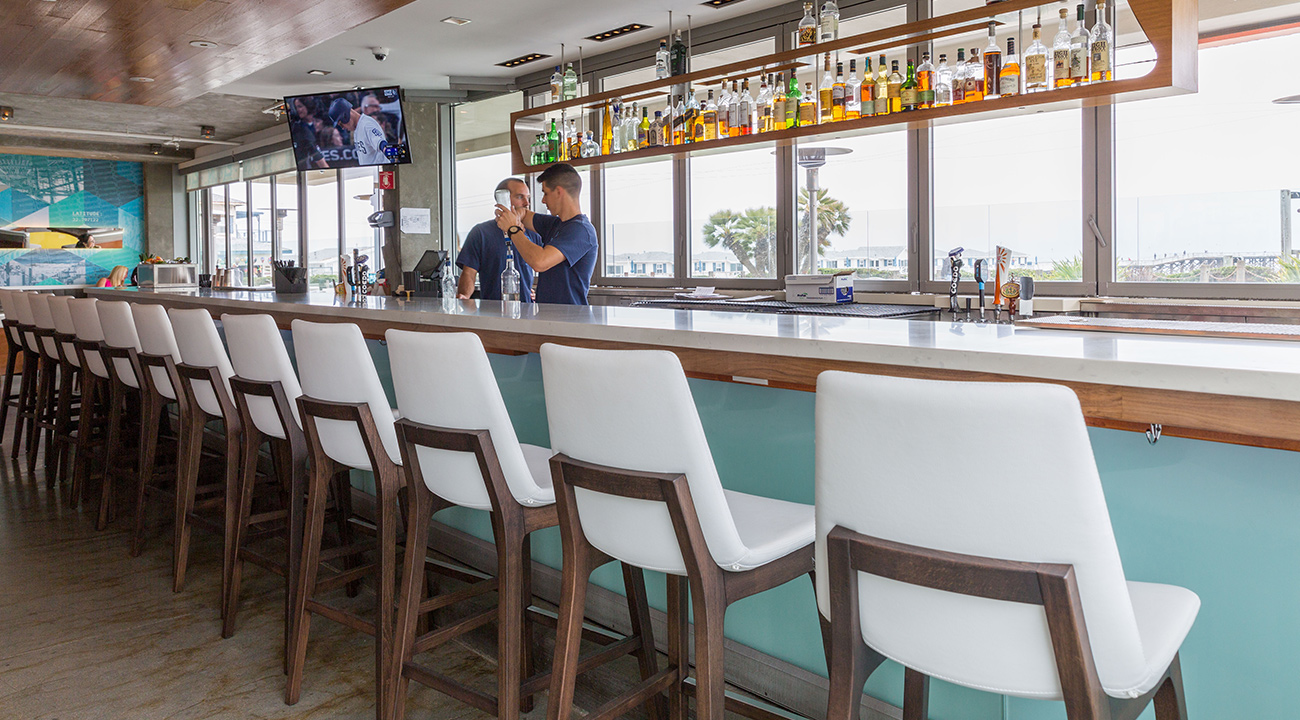 Bar at JRDN with white high top chairs and view of the ocean