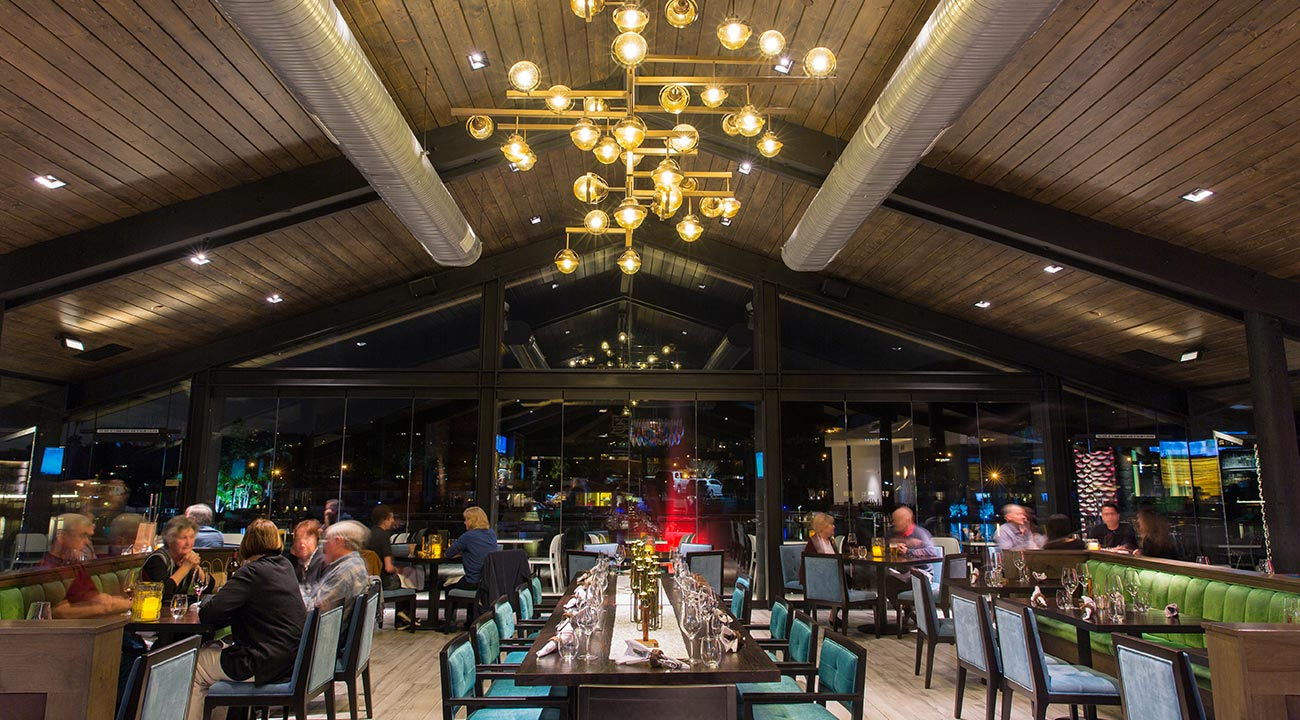 Decoy restaurant dining area featuring a tall wooden ceiling, gold modern light fixture, velvet teal seating with velvet green booths with scattered guests seated at the tables eating