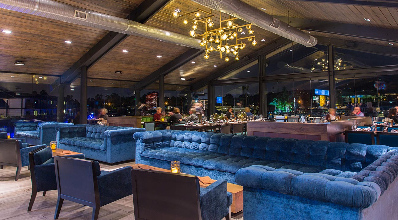 Decoy Restaurant lounge area with puffy blue velvet sofas underneath a gold modern light fixture with guests dining in the background