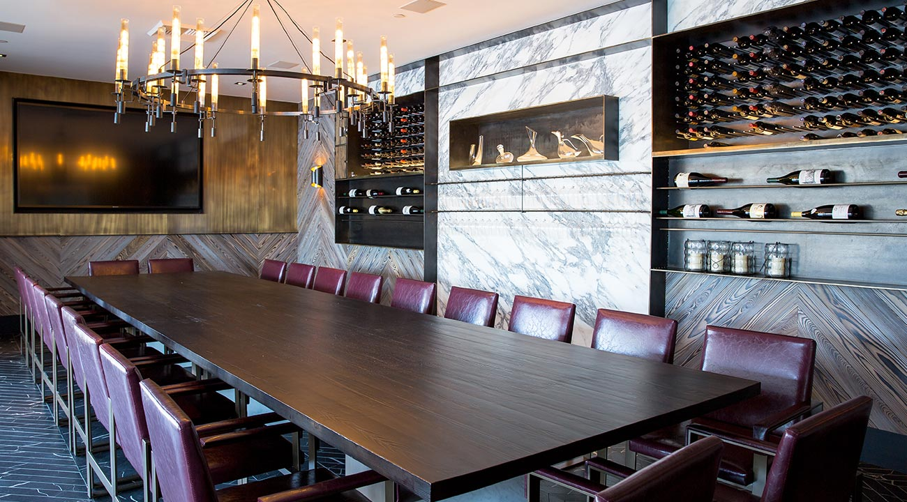 Large wooden table surrounded by brown leather chairs underneath a chandelier next to a white marble wall wine rack and a mounted tv