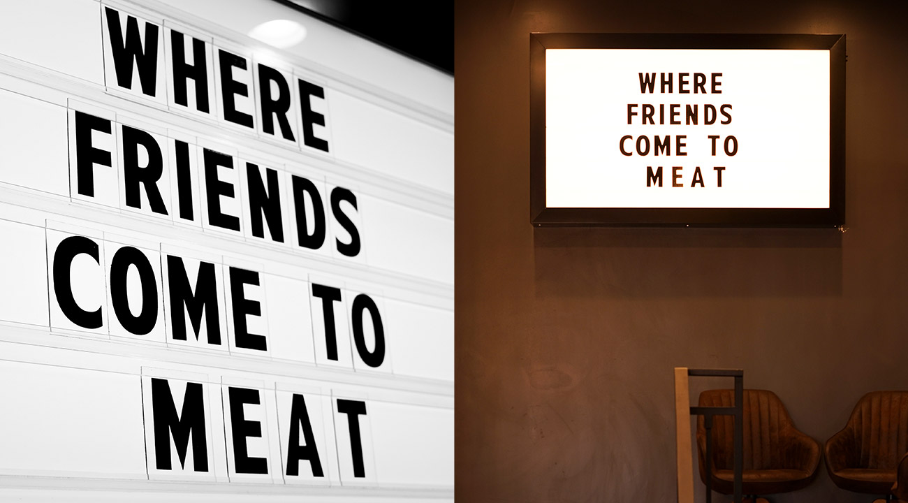 """LED light box mounted on restaurant wall that says """"Where friends come to meat,"""" spelled M-E-A-T"""