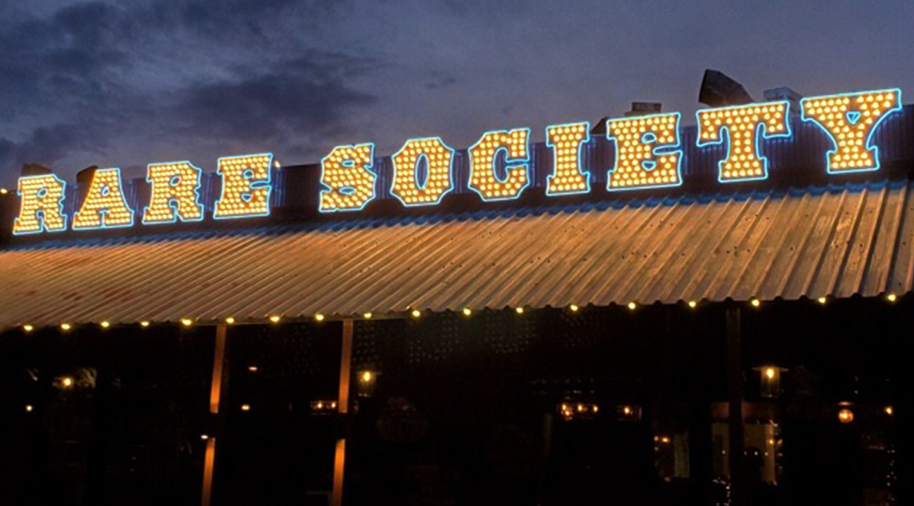 Exterior of restaurant at night with Rare Society sign spelled out in vegas-style lettering