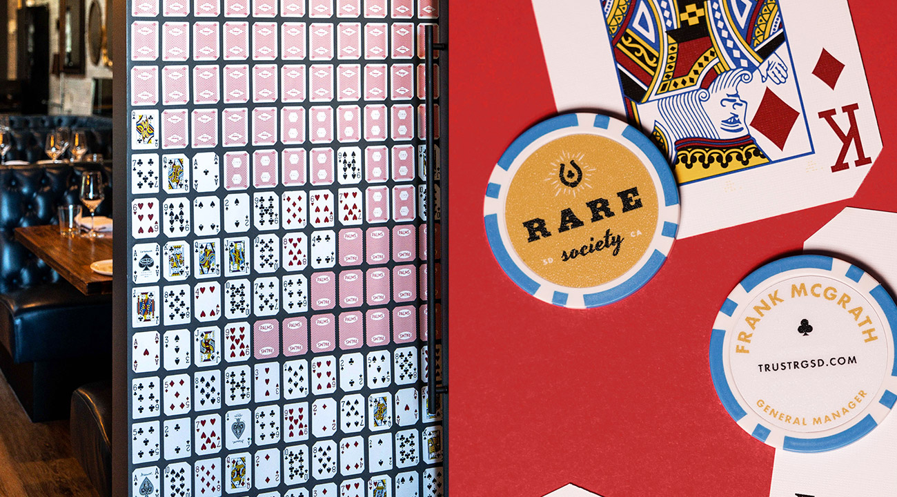 """Dipdick of Rare Society custom playing card wall installation next to Rare Society blue and gold poker chip business """"cards"""" against a king playing card and red background"""