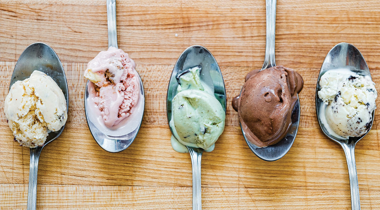 5 spoons of 5 different scoops of ice cream laying on wooden table